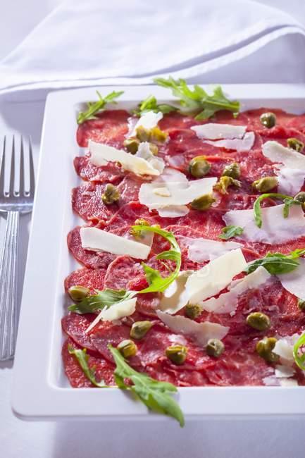 Карпаччо из кусочков сырой говядины — стоковое фото