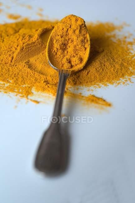 Turmeric powder on spoon — Stock Photo