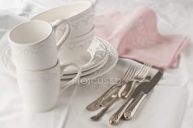 Vista elevada de vajilla blanca y cubiertos de plata - foto de stock