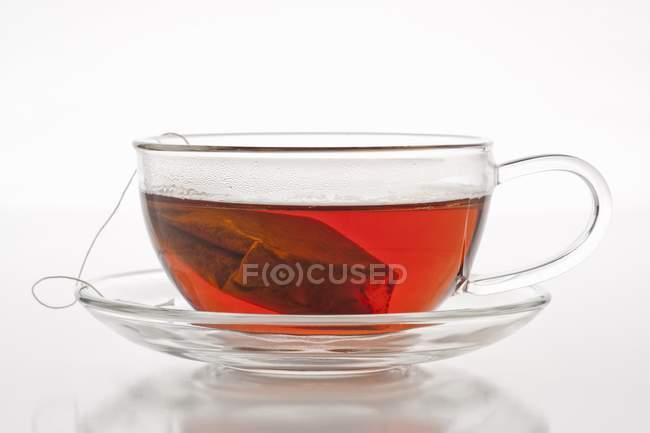 Thé avec sachet de thé dans une tasse en verre — Photo de stock