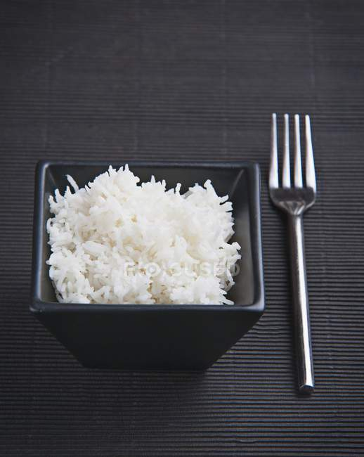 Cooked rice in black dish — Stock Photo
