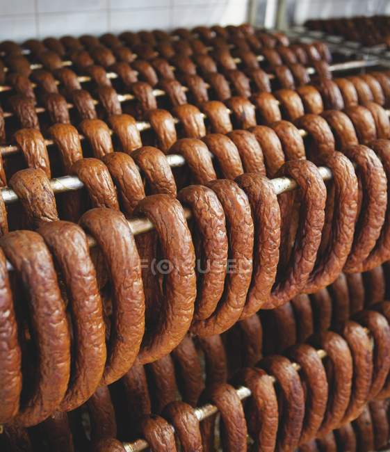 Sausages hanging on metal rack — Stock Photo