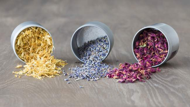 Dried marigold, lavender and rose petals in upturned tins — Stock Photo