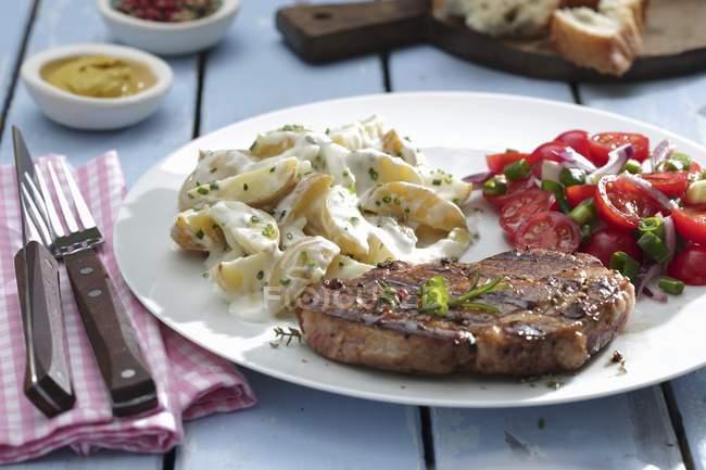 Pork with potato and tomato salads — Stock Photo