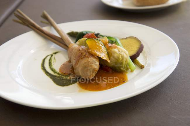 Pork belly and mashed potato roll with a cabbage leaf wrap on a stick of lemongrass served with pumpkin, asparagus, spinach and sweet potatoes — Stock Photo