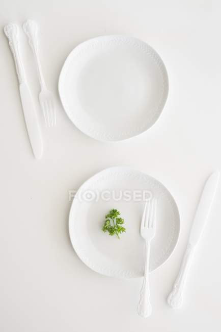 Top view of white plates, cutlery and parsley — Stock Photo