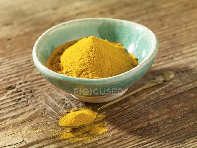 Turmeric powder in bowl and on spoon — Stock Photo