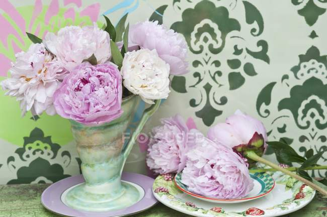 Pink peonies in a retro vase and on a plate against a wall decorated with a stencil pattern — Stock Photo