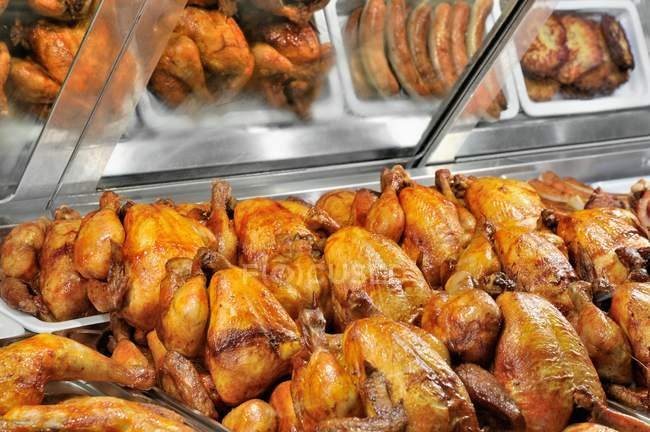 Closeup view of grilled chicken and other grilled meats in a fast food display — Stock Photo