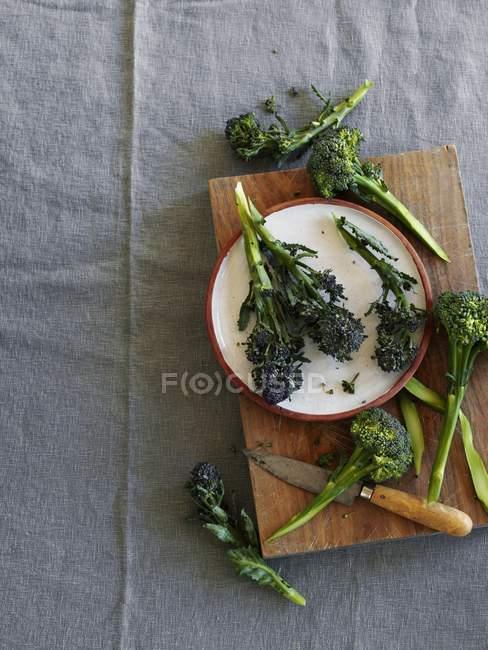 Brócoli fresco en una tabla de cortar y en un plato - foto de stock