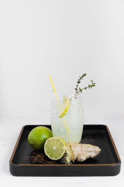 Vista de cerca de jengibre y refresco de lima con ingredientes en una bandeja barnizada - foto de stock