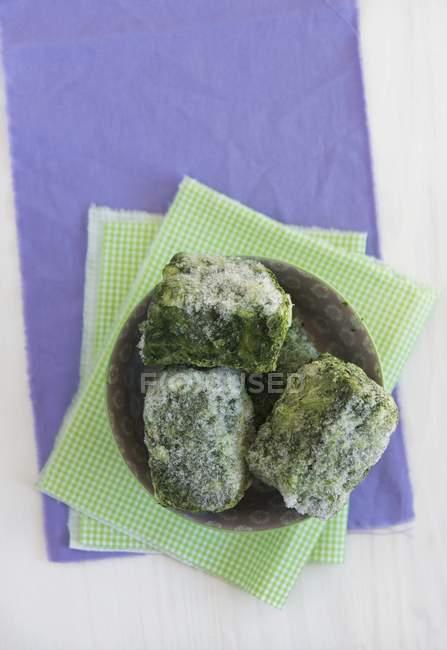 Заморожені шпинат порцій на плиті над зеленим рушник — стокове фото