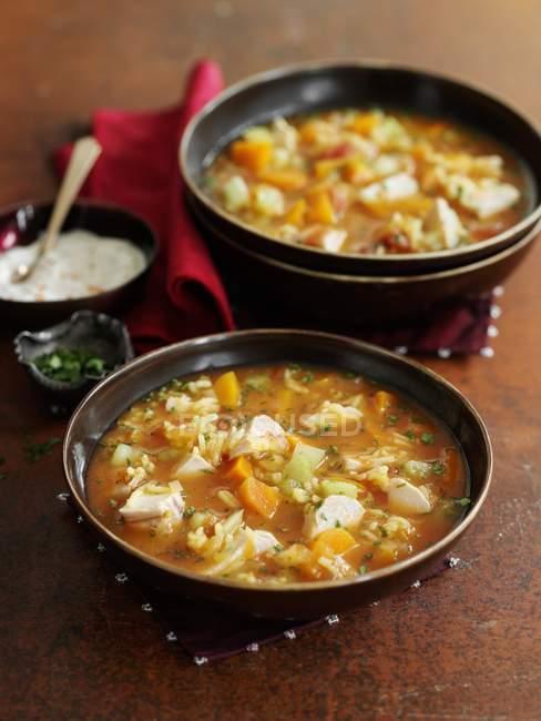 Mulligatawny - curry-Suppe mit Huhn und Gemüse in schwarzen Platten über Holzoberfläche — Stockfoto