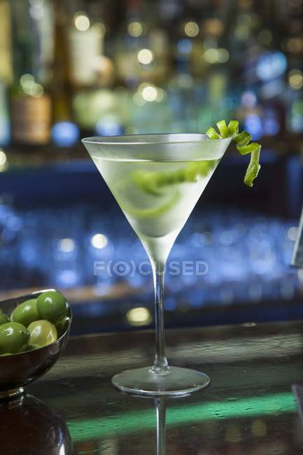 A Gimlet coctail in glass with vegetable over table in bar — Stock Photo