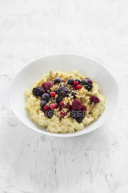 Creamy millet porridge with berries and nuts — Stock Photo
