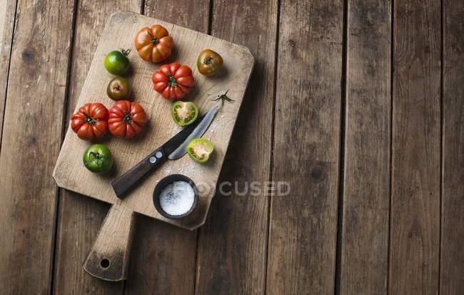 Varios tomates en una tabla de cortar con sal y un cuchillo sobre la superficie tejida - foto de stock