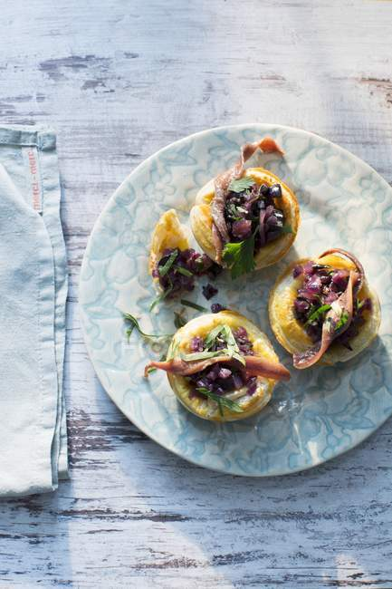 Onion and anchovy tartlets on plate — Stock Photo