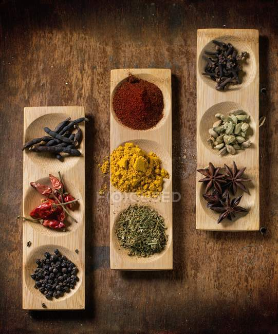 Various spices in wooden dishes on wooden surface — Stock Photo