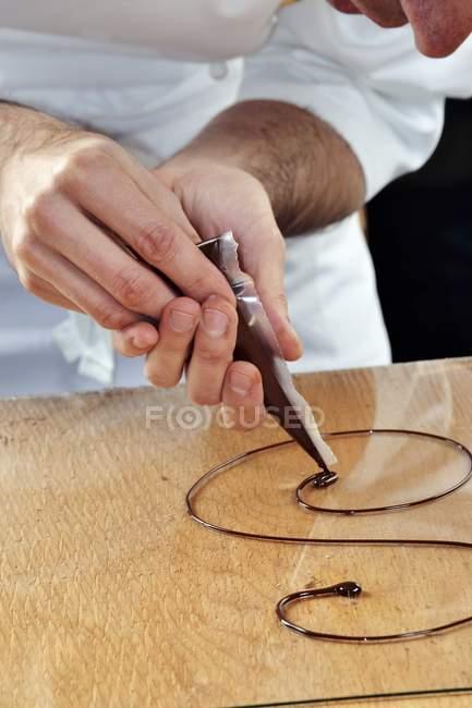 Primer plano vista recortada del dibujo del hombre con salsa de chocolate en bandeja de cristal - foto de stock