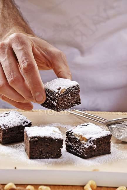 Mano che tiene uno dei brownies con zucchero a velo — Foto stock