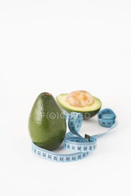 Fresh avocados with measuring tape — Stock Photo