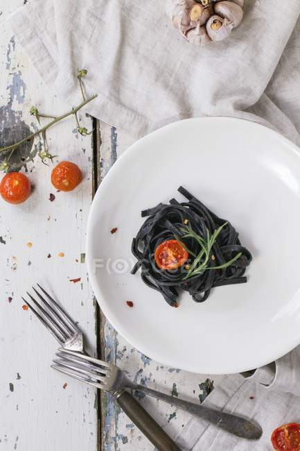 Black tagliolini pasta with baked tomatoes — Stock Photo