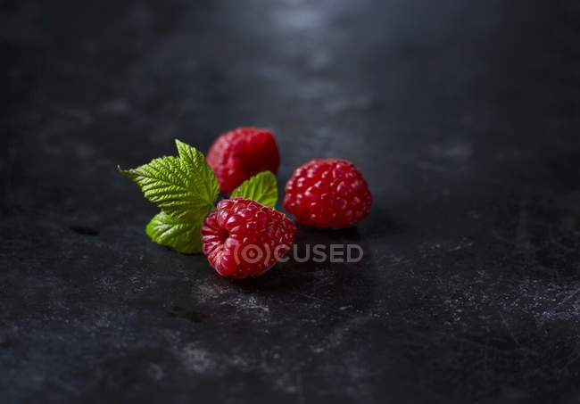 Fresh raspberries with leaves — Stock Photo