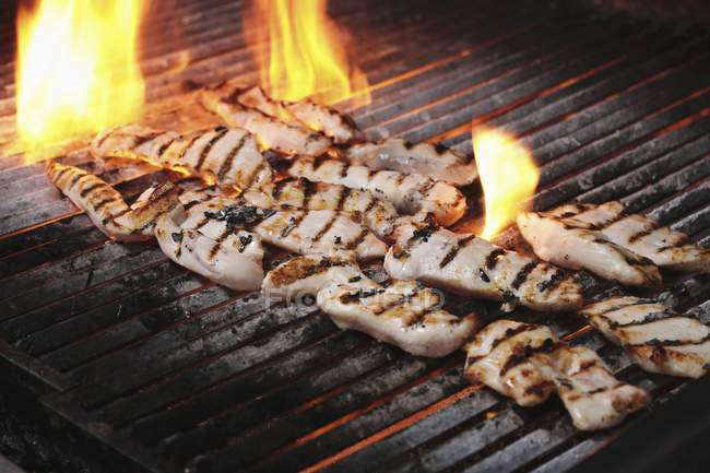 Chicken fillets on grill — Stock Photo