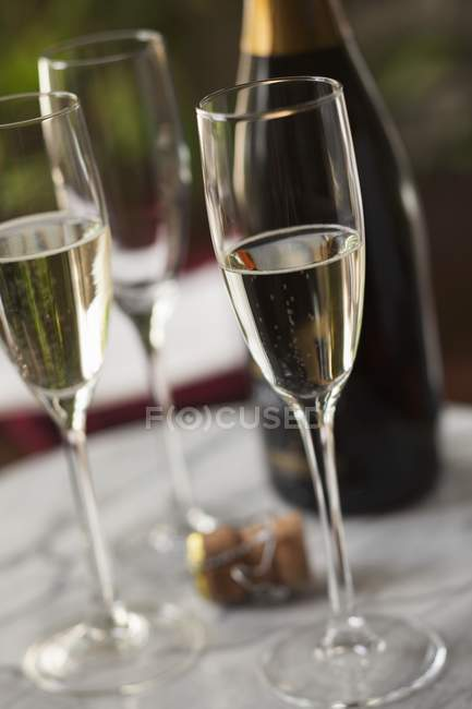 Glasses of champagne with the cork — Stock Photo