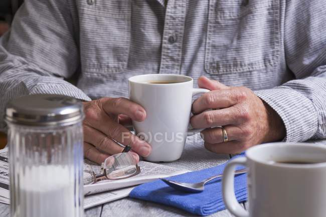 Cropped view of man holding cup of coffee over newspaper — Stock Photo