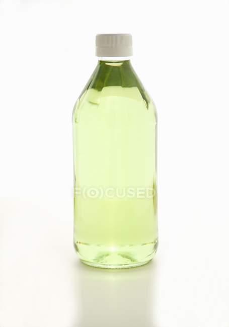 Closeup vista de uma garrafa de óleo de semente de uva sobre uma superfície branca — Fotografia de Stock