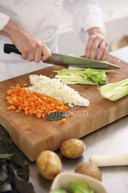 Uno chef a dadini verdure con coltello in mano tagliere — Foto stock