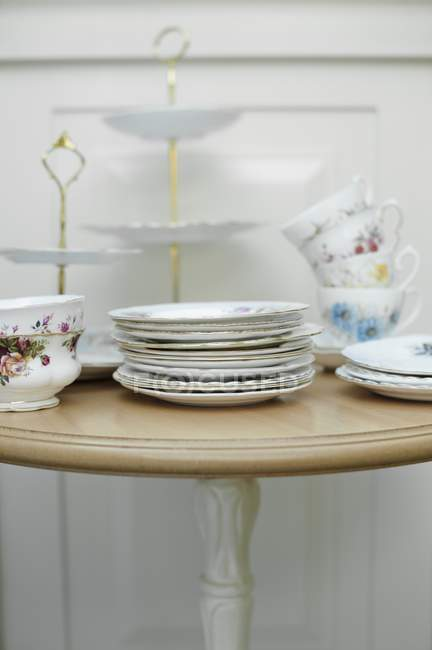 Vintage crockery including plates, cups and a cake stand on a table — Stock Photo
