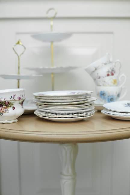 Louças vintage, incluindo pratos, copos e um carrinho do bolo em uma tabela — Fotografia de Stock