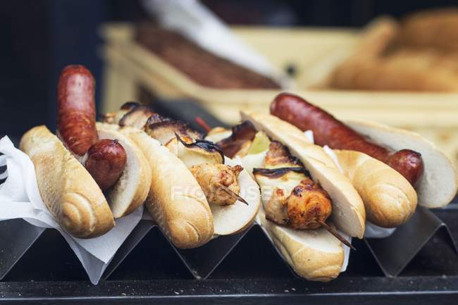 Hot dogs and grilled chicken skewers — Stock Photo