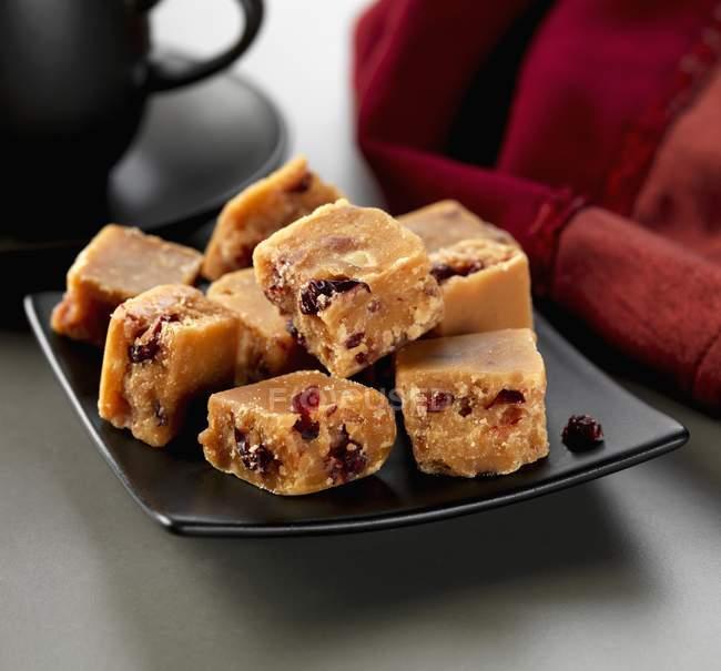 Closeup vista pedaços de Fudge cranberry na placa quadrada preta — Fotografia de Stock