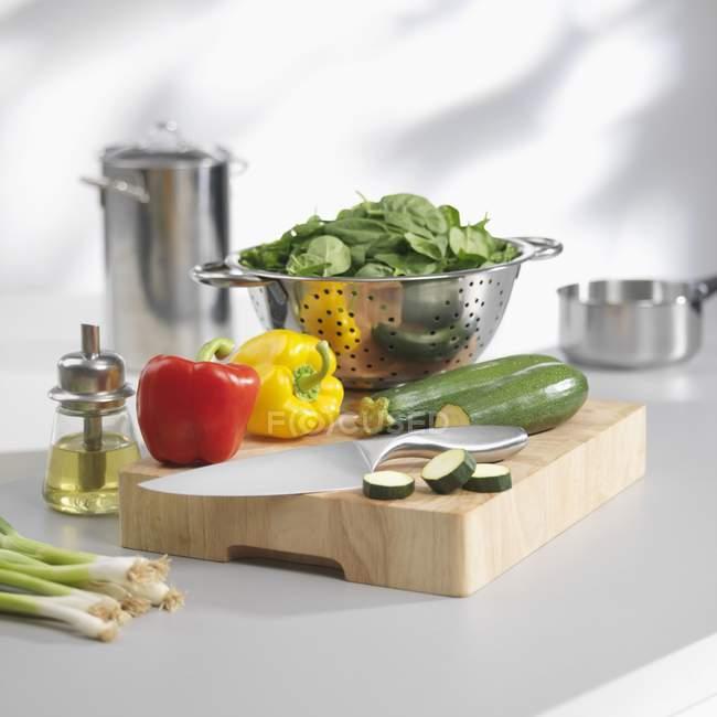 Épinards dans une passoire et légumes sur une planche à découper — Photo de stock