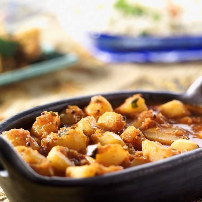 Würzige Kartoffel-curry in schwarzer Schale — Stockfoto
