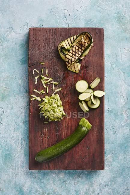 Courgette: intera, affettata, grattugiata e grigliata su tavola di legno — Foto stock