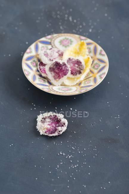 Closeup view of candied rose petals on plate and dark surface — Stock Photo