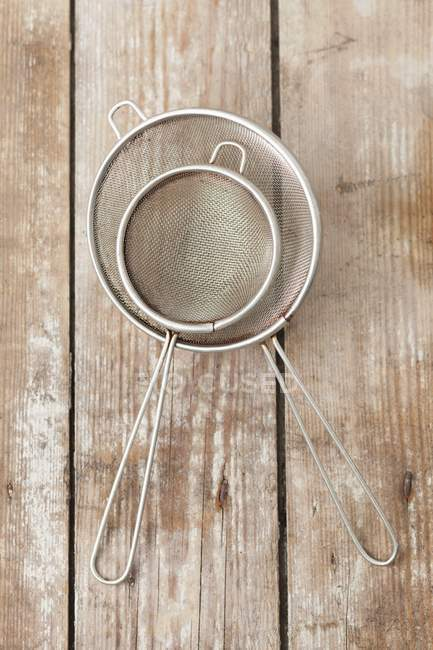 Closeup top view of old metal sieves on a wooden surface — Stock Photo