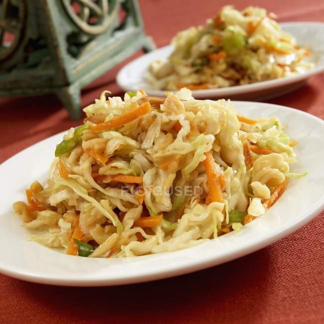 Salade de chou orientale sur plaque blanche sur surface rouge — Photo de stock