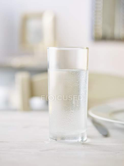 Closeup view of chilled water glass on white surface — Stock Photo