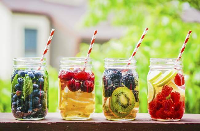 Closeup view of four fruity drinks in screw-top jars on a garden table — Stock Photo