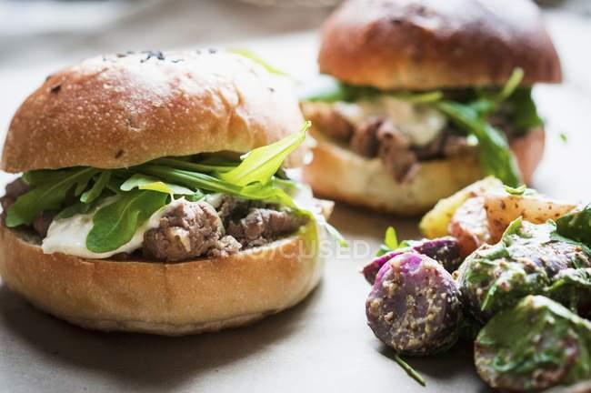 Hamburguesas de carne con queso y cohete - foto de stock