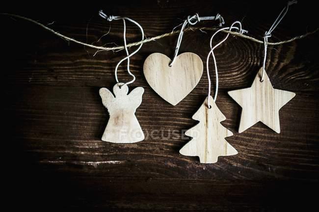 Vista superior de decoraciones navideñas de madera en cuerdas - foto de stock
