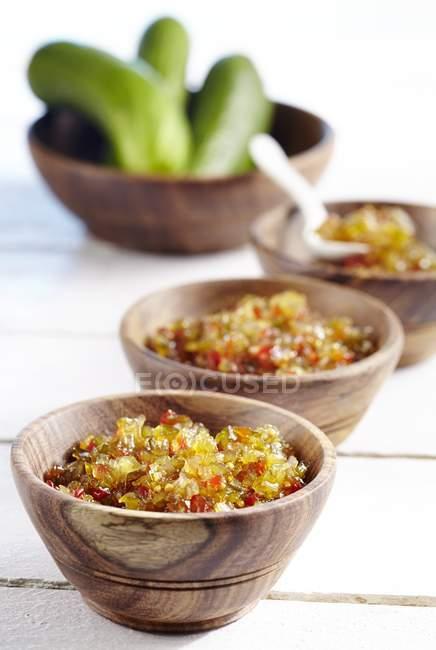 Cetriolo gusto con peperoni in ciotole di legno su superficie di legno — Foto stock