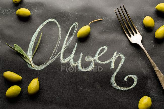 Scattered olives and a fork around the work 'Oliven' — Stock Photo