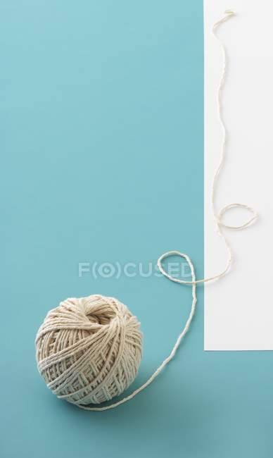 Closeup view of a ball of twine on a light-blue surface — Stock Photo