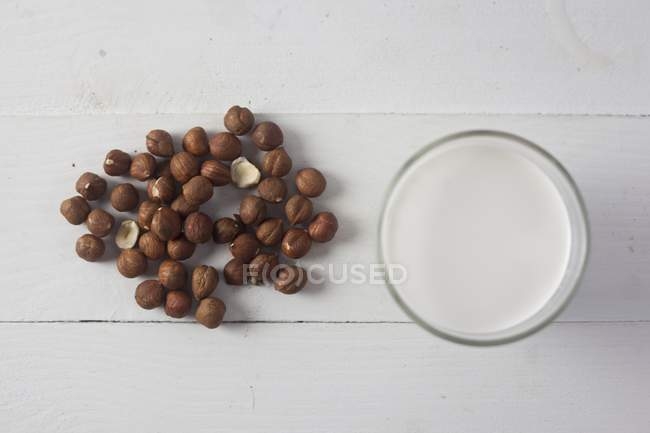 Haselnussmilch auf weißer Oberfläche — Stockfoto